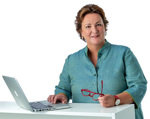 Claudia Behrens-Schneider - Seminare - Beratung - Coaching - Gauting - Claudia Behrens-Schneider vor Laptop mit roter Brille und grüner Jacke