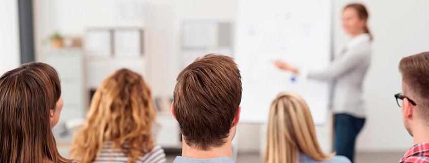 Claudia Behrens-Schneider - Seminare - Beratung - Coaching - Gauting - Frau hält vor einer Gruppe an der Flipchart einen Vortrag